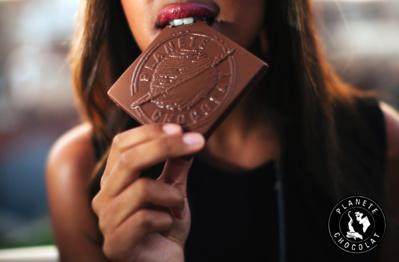 Femme qui croque dans un carré Planète Chocolat©
