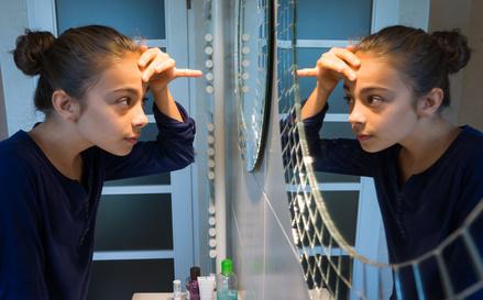 Adolescente se regardant dans le miroir©