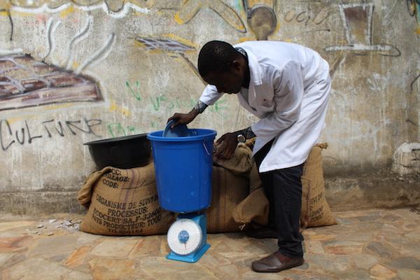 Un travailleur de Choco Togo pèse des féves de cacao©Roger Adzafo , Espoir Kodjo